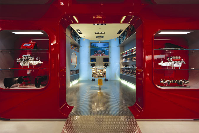 Ferrari red is the cohesive design element along with curvilinear lines for displays, in the Ferrari shops worldwide, designed by an Italian architect.
