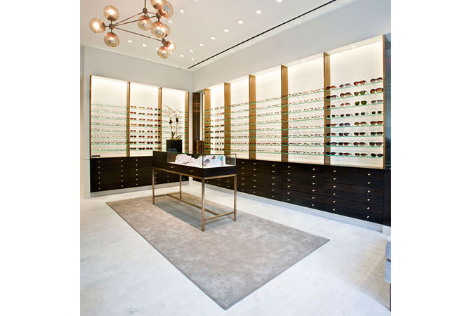 Here in the Robert Marc eye glass shop a chandelier made of clustered, seeded glass globes, is a strong design element. The cabinetry consists of clean-lined walnut stained drawers, to contrast with the bright back lit wall display.
