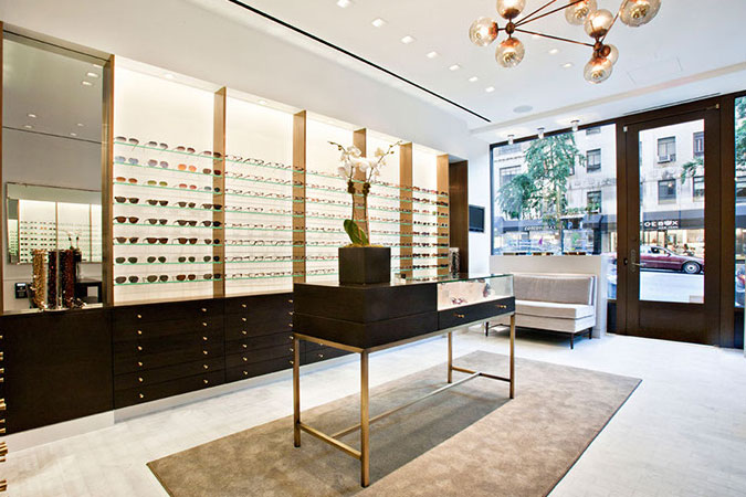 A mid-century inspired white sofa sits at the front of the Robert Marc eye glass shop, with it's elegant clean lines, and an approach to product display that is graphic and artistically done.