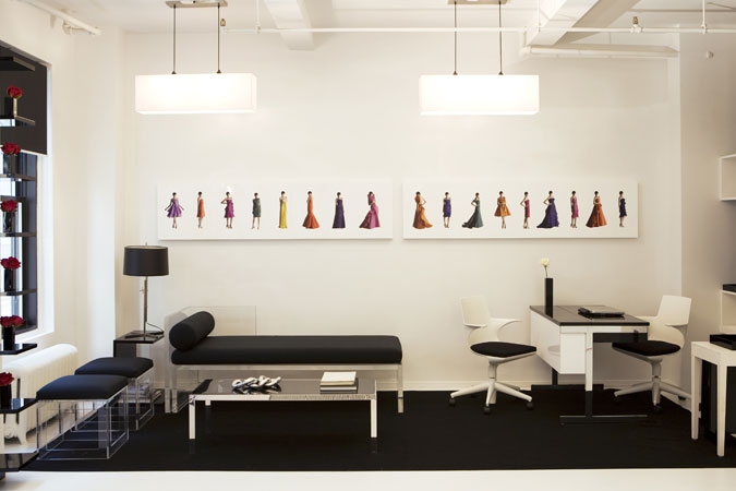 The waiting area for a fashion designer's showroom features  images of his latest work, displayed on a white acrylic box.