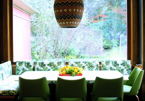 A floral upholstered banquet with chairs covered in a deep mossy green bring the outdoors in, at a breakfast table.