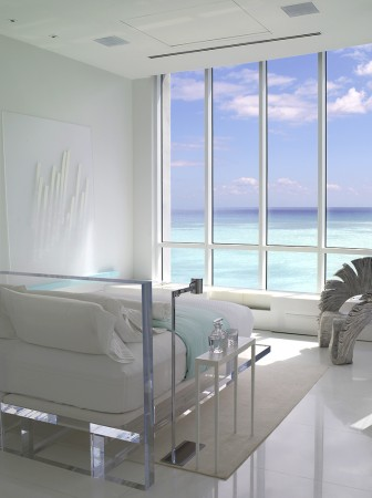 In a Miami master bedroom, serenity, privacy and the creation of  a zen-like atmosphere, be it morning or evening was the goal, along with a total ocean front experience. A custom lucite bed floats in the space