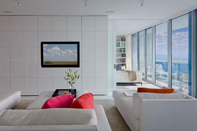 A flat screen television is inset into the all white grid patterned walls, which were elegantly lacquered.