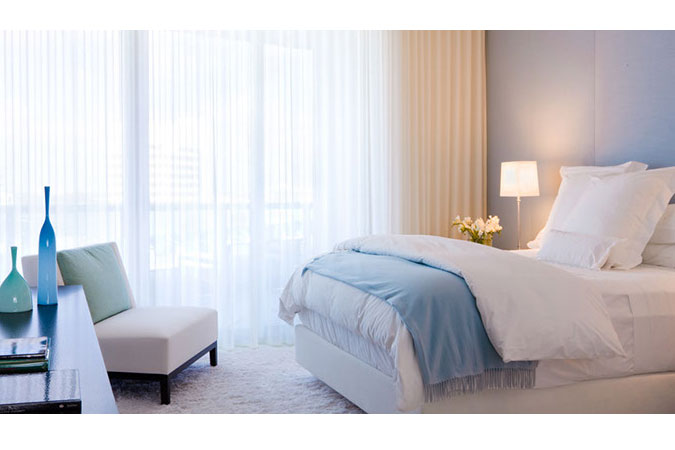 Restful tones in a bedroom create a welcoming and restful place, when the hot sun and beach are beyond the window.