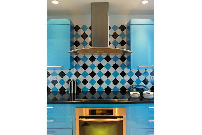 A vibrant kitchen in a Canyon Ranch condo on Miami Beach. Here, turquoise lacquer cabinetry mix with tile in a diamond pattern of black, white and turquoise..