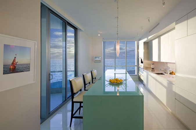 The focal point of a kitchen in Miami is a sandblasted glass center island which has been sleekly designed to comingle, but not distract from the wrap around views.