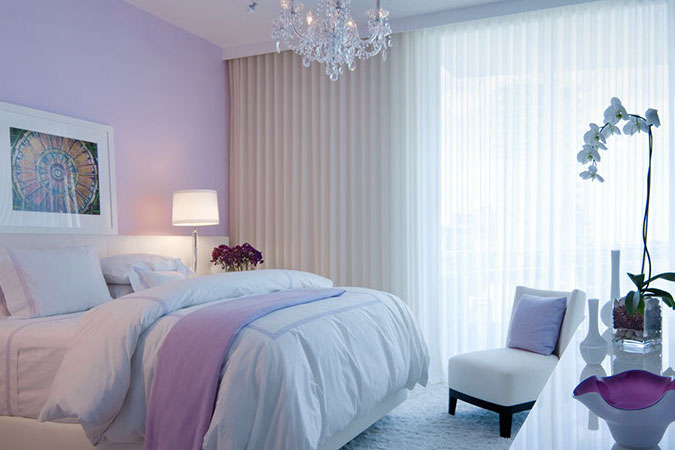 Absolute elegance, with sheer draperies, chandelier hung over the bed,  and plush linens. The pale lavender and white palette elevates  it to perfection.