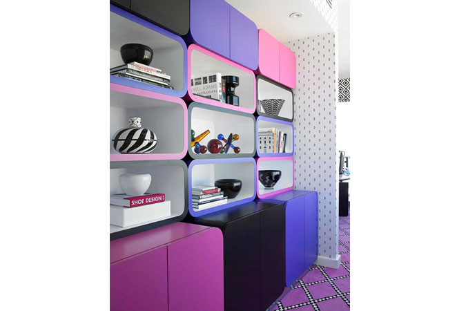 A home office in a Miami condo, uses pink, black and purple for the built-in cabinetry for storages and to display objects.