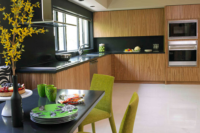 A Miami Beach kitchen pairs zebra wood cabinetry with black Corian, and bold chartreuse chairs are pulled up to  a black stone table.