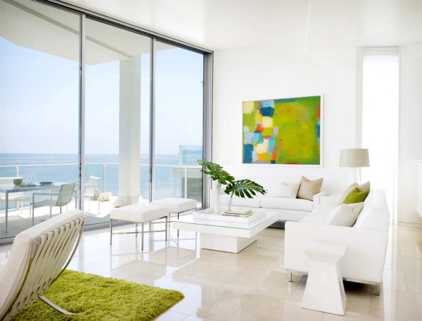 Pops of color enliven the living room in this all white contemporary beach house on the ocean in Malibu, California.