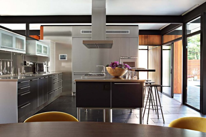 A custom stainless steel German kitchen has been seamlessly integrated into the open plan of this mid-century home.