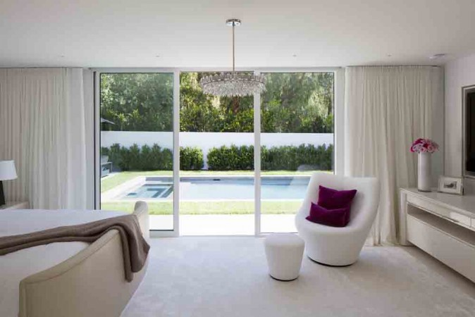 A serene master bedroom is adjacent to the pool. Made sumptuous with a leather Bed by J. Robert Scott, and accented with a mocha colored Italian cashmere throw. A white velvet upholstered chair is in keeping with a crystal pendant fixture, from the 1960s.