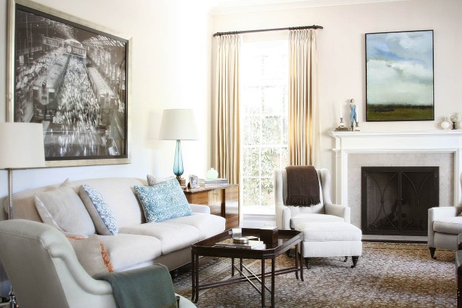 The classic bones of the house were respected,  and clean lined furniture, black and white photographs and natural linen provide comfort, and ease.  The carpet and draperies make the room informally elegant.