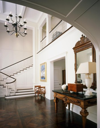 The double height ceiling gives way to the grand entry, with walls accented with the homeowner's  elegant antiques as well as the drama of the wide staircase.