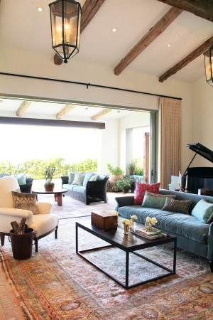 This Spanish Colonial style home on the bluff over looks the beach, while matching colored sofas and exposed beams elongate the space.