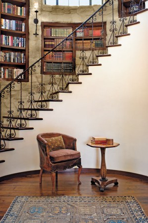This Santa Barbara home features a winding staircase, accented with a stone-walled bookshelf installation and a detailed iron railing.