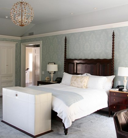 This bedroom has a modern spin on early 20th century style. The chandelier hangs over the bed, which proudly displays a two-posted headboard serving as the focal point of the room. The stenciled walls evoke a rich and comforting feeling, while the most modern piece of all, the leather upholstered ottoman, sits at the end of the bed.