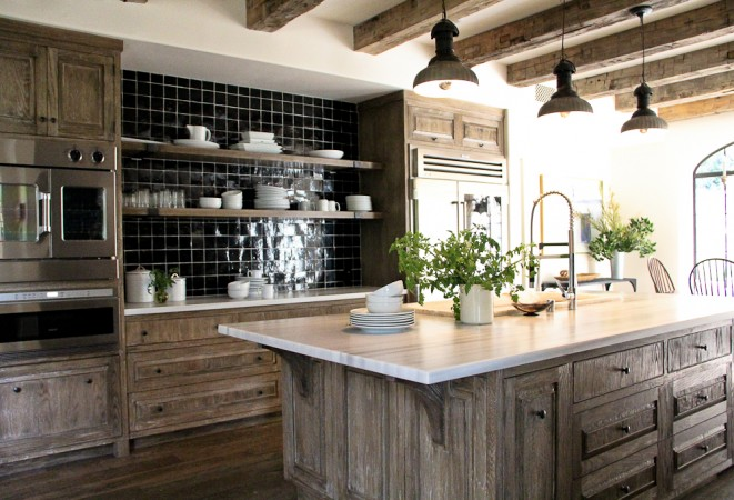 The limed oak cabinetry brightens up the kitchen and antique beams were brought in to accent the space.  Open shelving units were left open letting more of the black tiled backdrop highlight the white dinnerware.