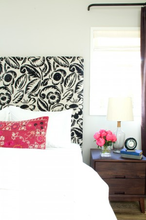 A bold and very graphic patterned headboard mixes with a fuschia toned print pillow, with all white bedding.