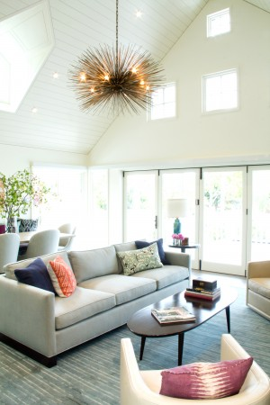 The Jean de Merry fixture is the newest addition and focal point of the room. The highly placed windows, above the double doors add extensive natural light. A pale blue- gray  covered sofa is equally soothing, with tiny pops of color from pillows.