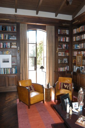 A library with vintage leather French chairs and a modern Tibetan rug.
