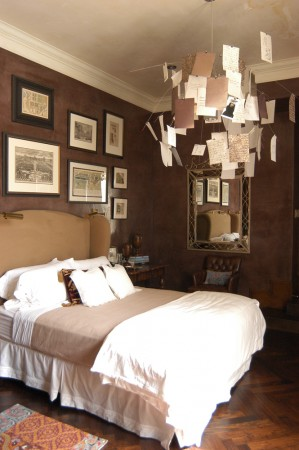 Here a guest ooom with a cashmere upholstered headboard and an Ingo Maurer chandelier that doubles as a guestbook.