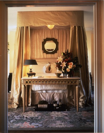 A William Morris inspired bedroom with a hand tufted rug and luxurious fabrics.