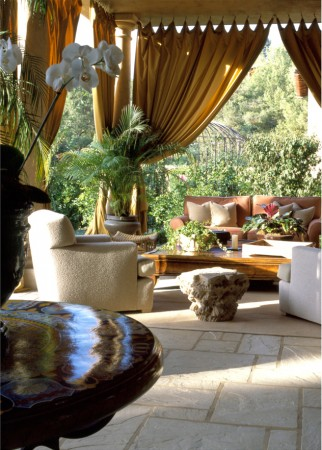 Using outdoor fabric for drapery to create an exterior room with custom made upholstery and antique found objects.