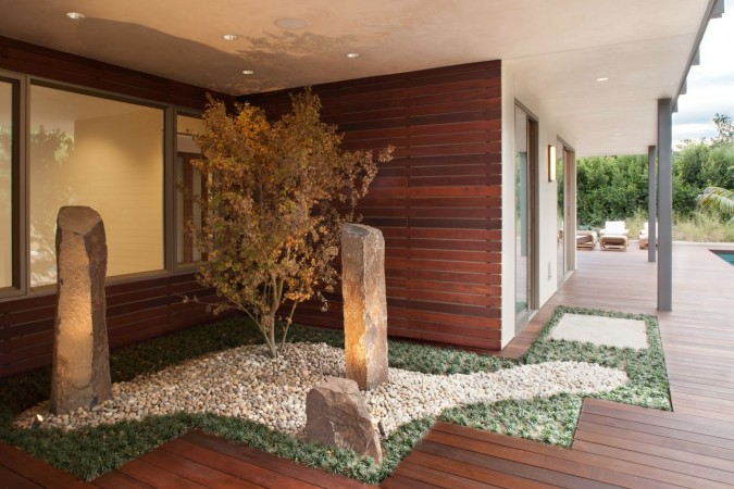 "The unexpected placement of this Zen-like sculpture garden draws the  landscape into interior spaces. It is the ""welcome home""  garden."